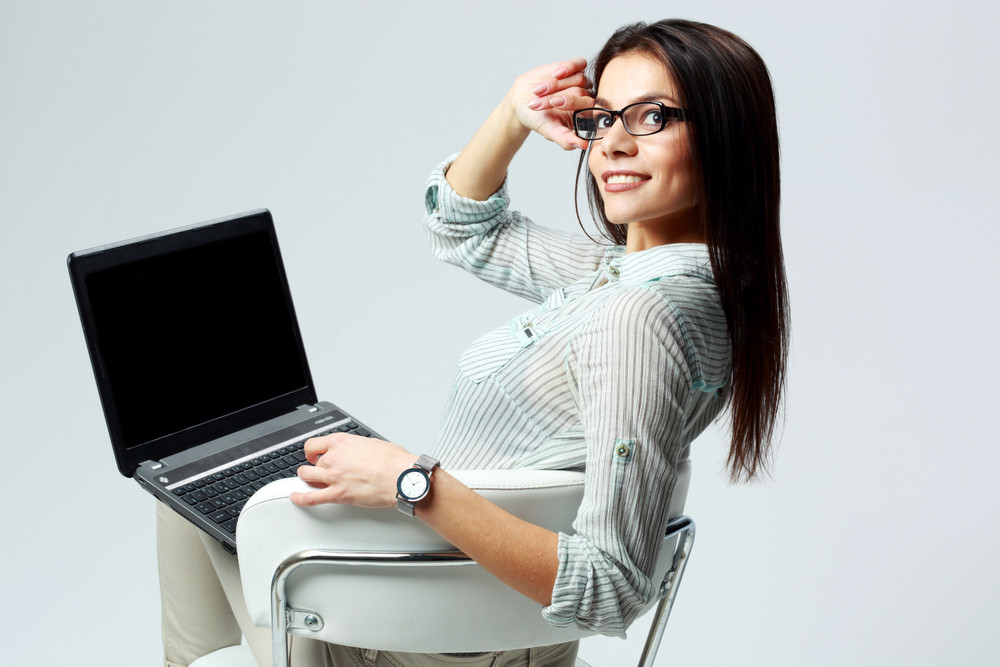 Young happy businesswoman sitting with laptop and looking at camera on gray background