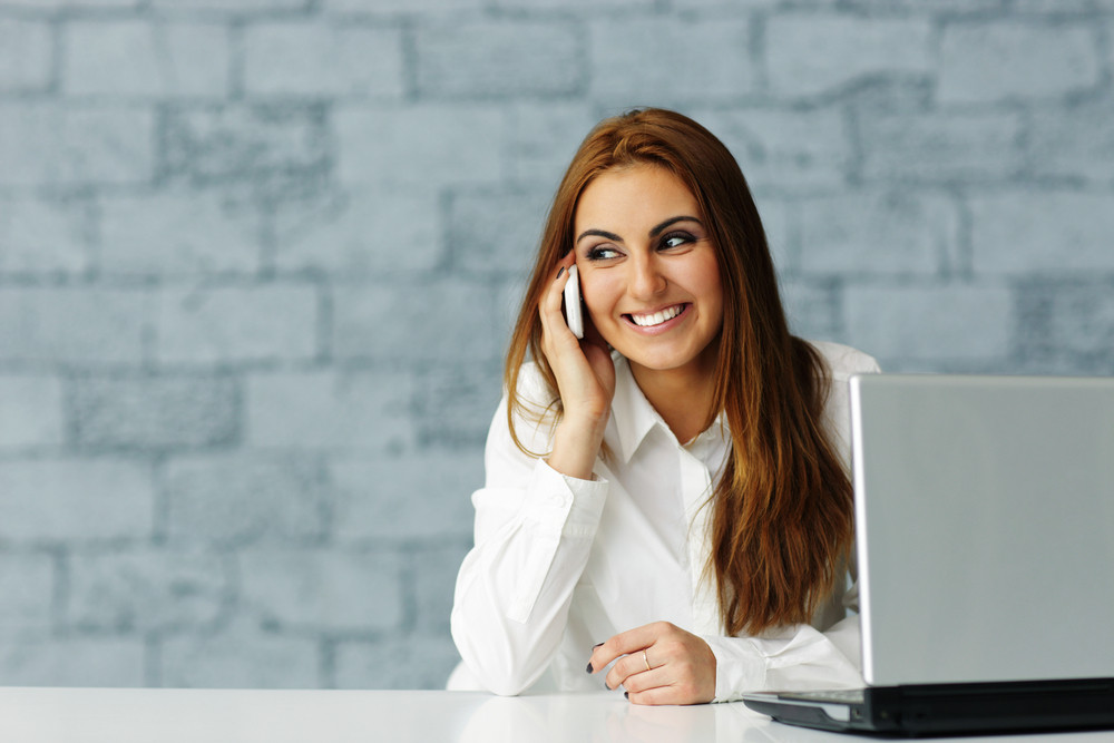 Young happy businesswoman talking on phone