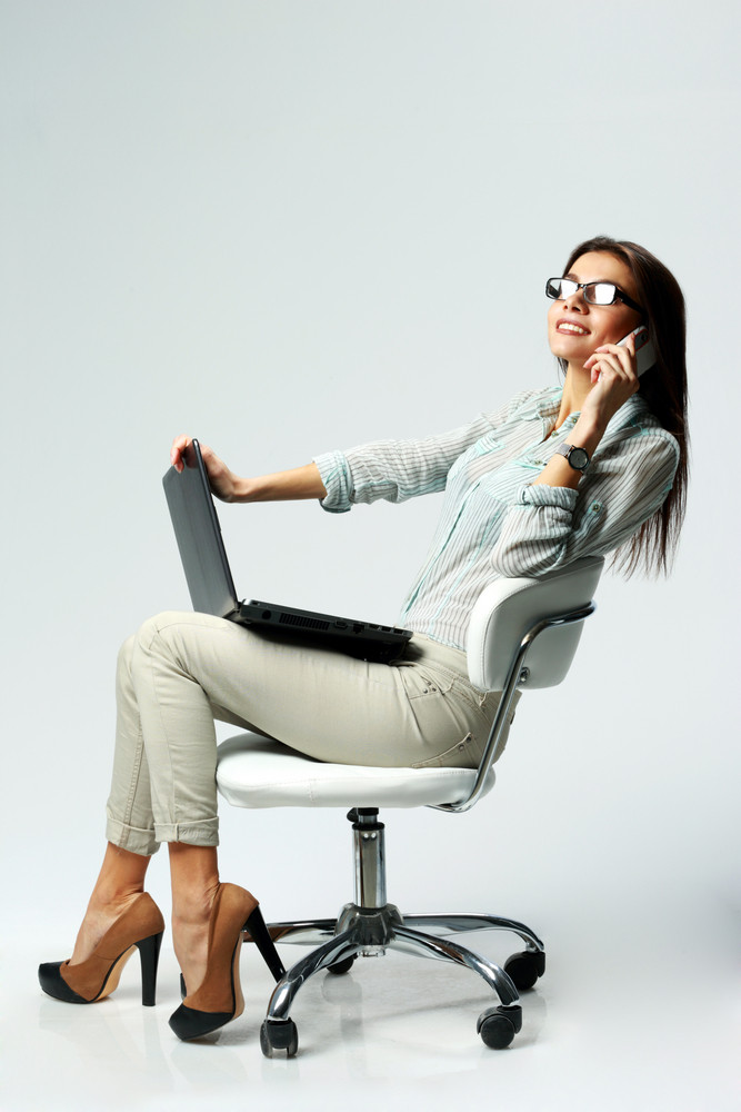 Young happy businesswoman using laptop and phone on gray background