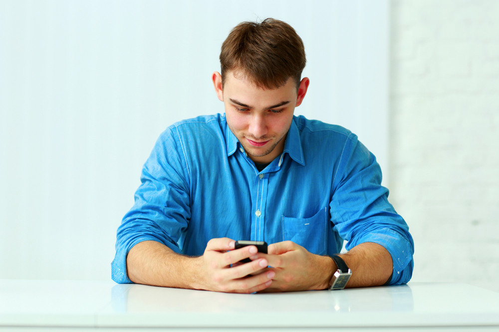 Young happy casual businessman sitting at the table and typing on smartphone in office