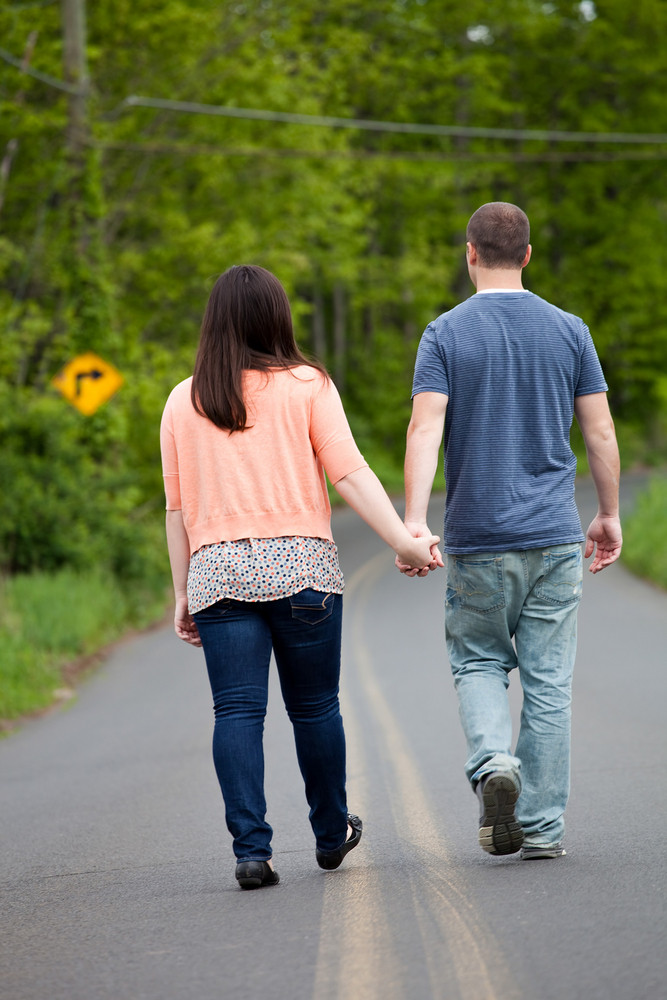 Young happy couple enjoying each others company outdoors walking down an empty road. A very fitting theme for the start of marriage or any romantic relationship.