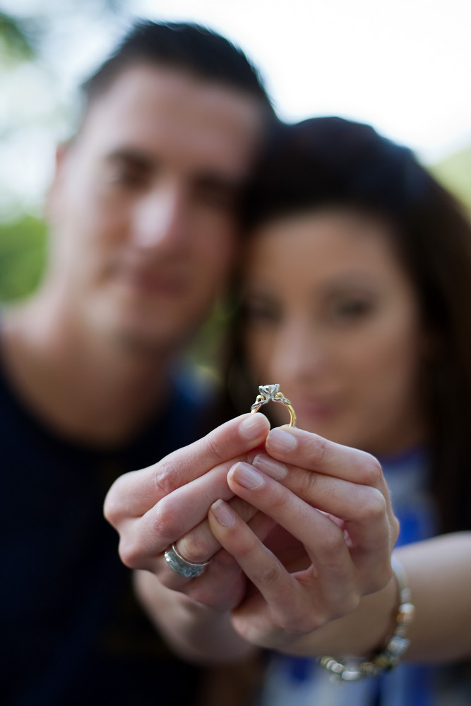 Young happy couple holding a diamond engagement ring.  Shallow depth of field with sharp focus on the ring.