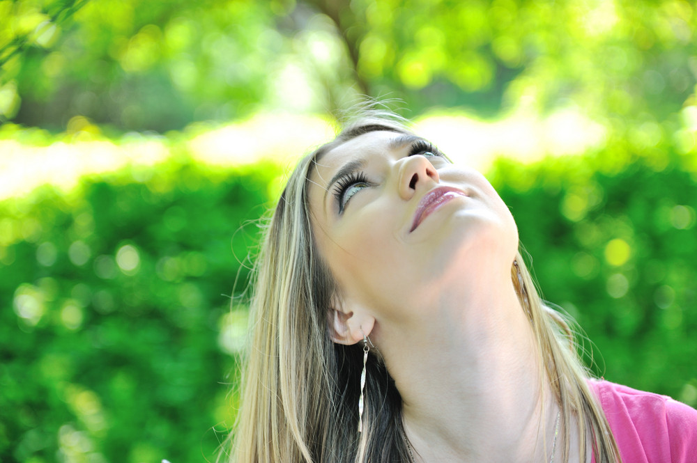 Young happy smiling woman looking up outdoors