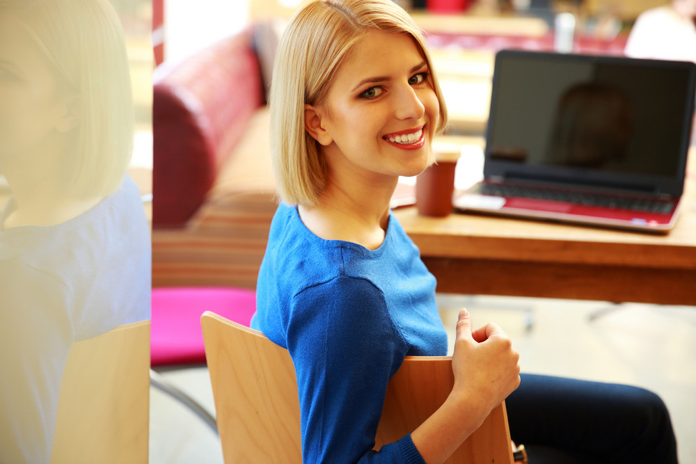 Young happy woman sitting at the table with laptop and looking at camera