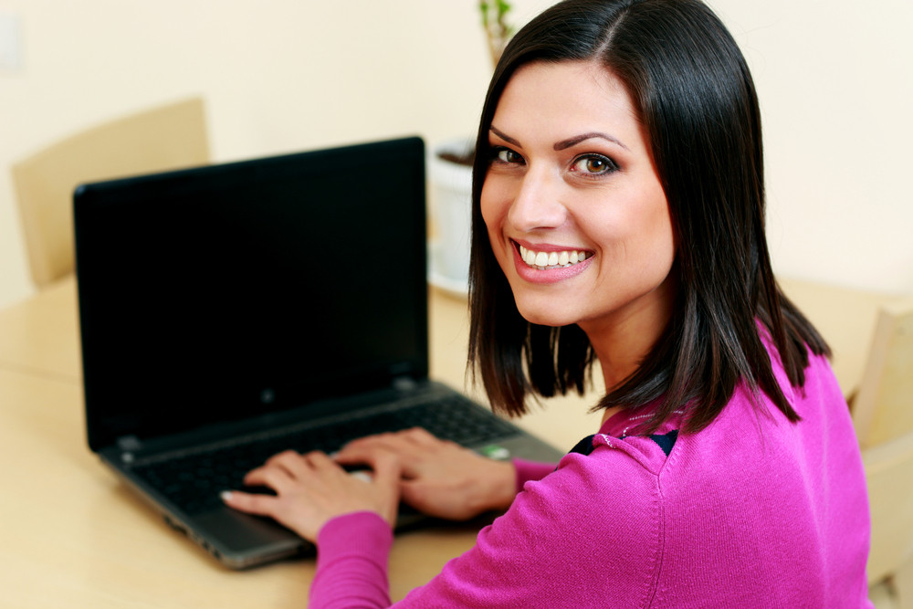 Young happy woman typing on the laptop and looking at camera