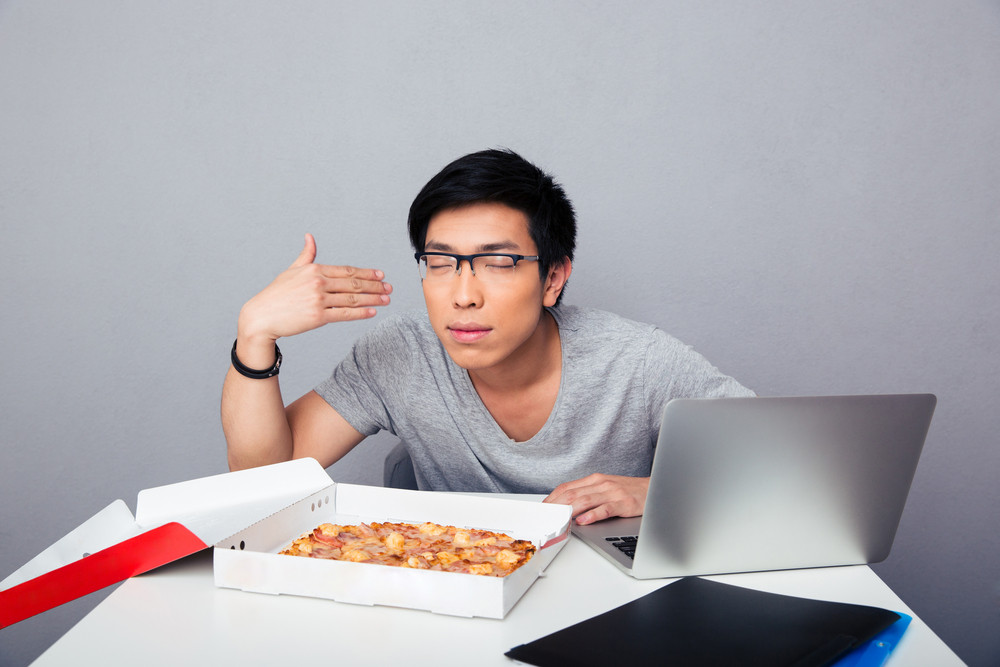 Young hungry man sitting at the table and smelling pizza
