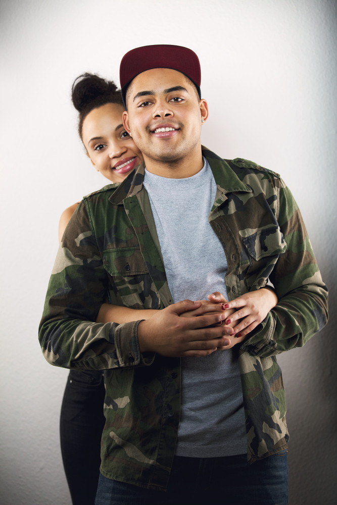 Young lady hugging her boyfriend from behind. Lovely young couple in love together on grey background.