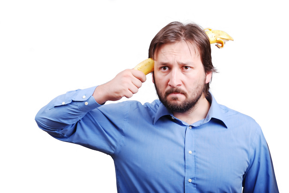 Young man blowing up his brain with banana