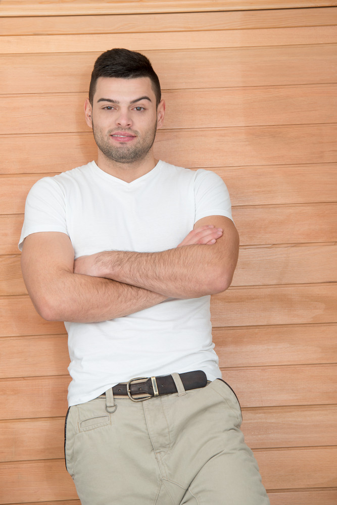 Young man in white shirt with his arms crossed in front of wooden background