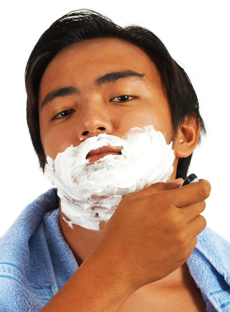 Junger Mann Rasieren im Spiegel
