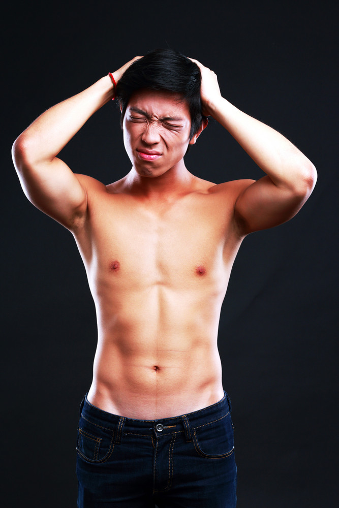 Young man suffering from headache on black background