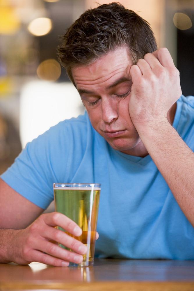 Young man with beer falling asleep at bar