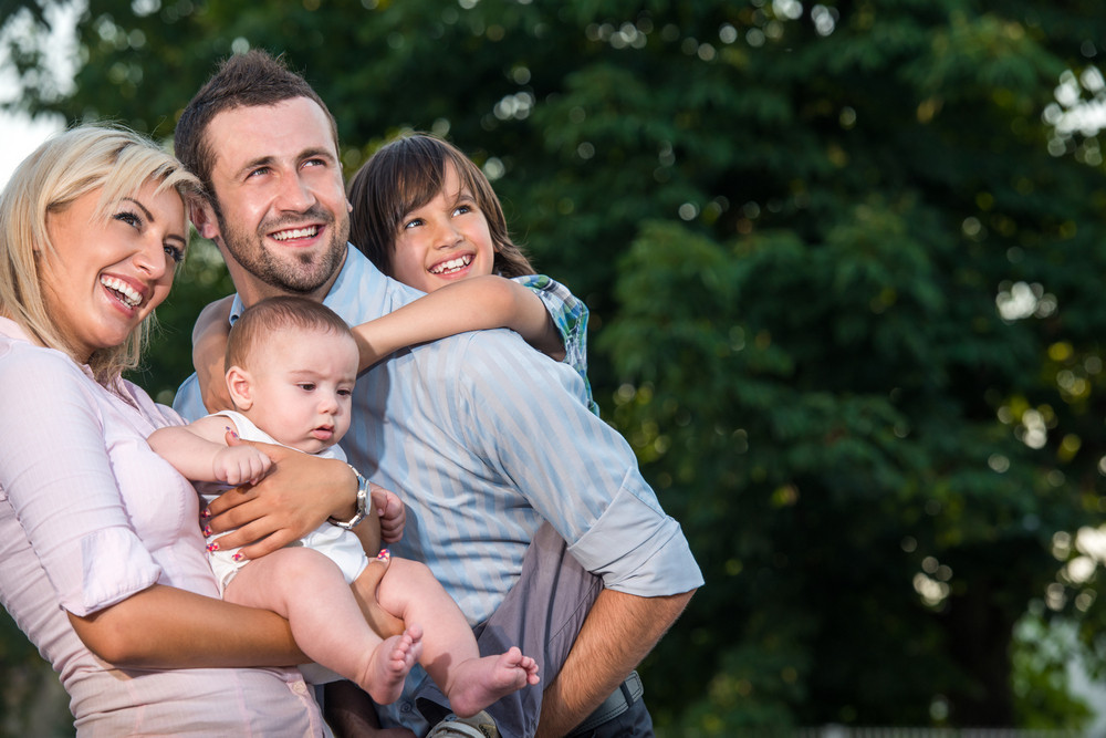 Young parents posing with two kids outdoors