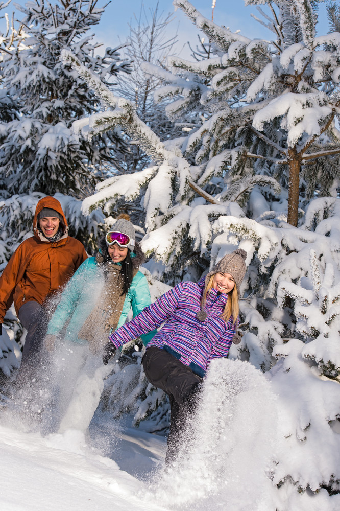 Young people having fun with snow laughing winter forest