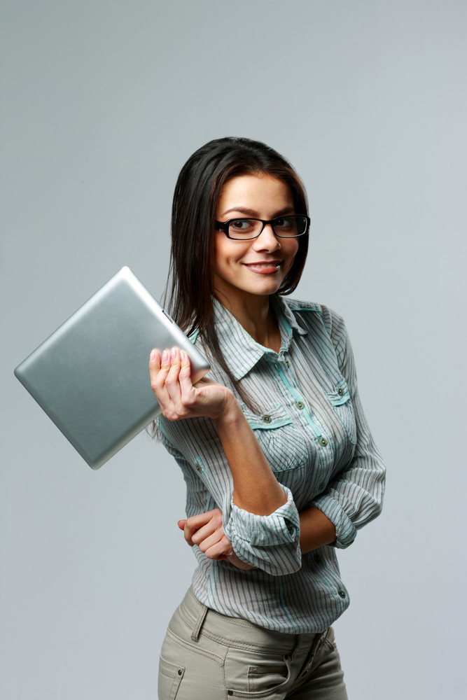 Young smiling businesswoman holding tablet computer on gray background