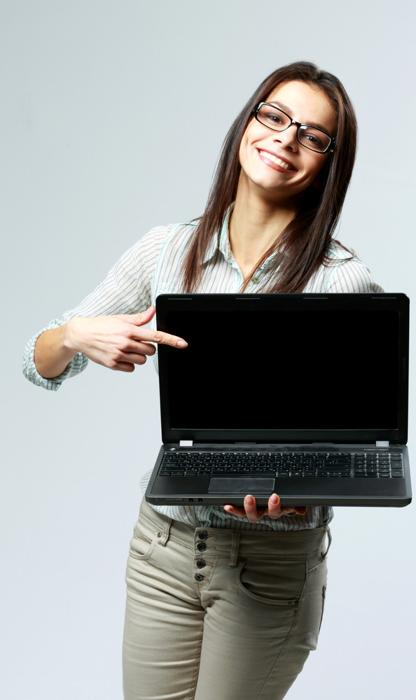 Young smiling businesswoman showing on a laptop screen on gray background