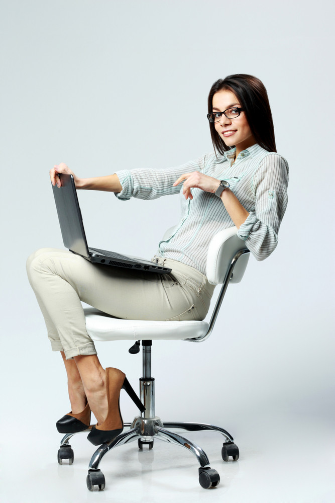 Young smiling businesswoman sitting on the office chair with laptop on gray background