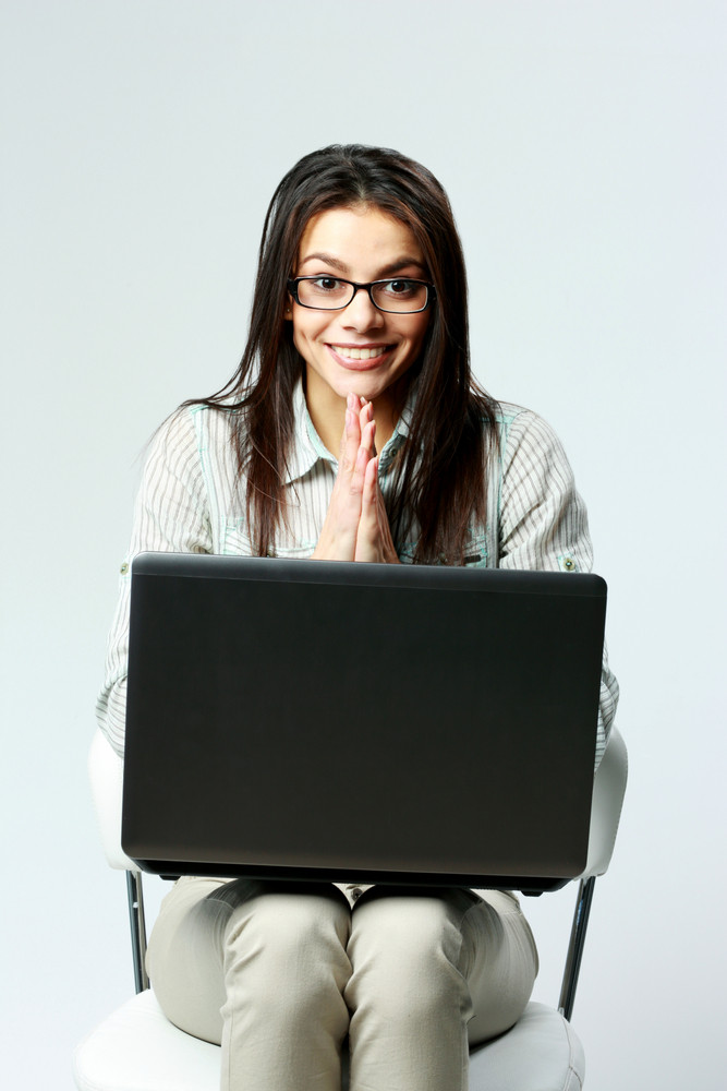 Young smiling businesswoman with laptop sitting on chair on gray background