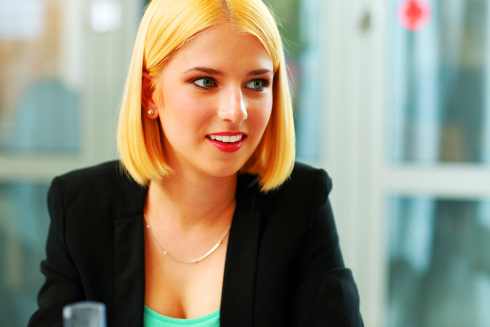 Young surprised businesswoman sittign at office