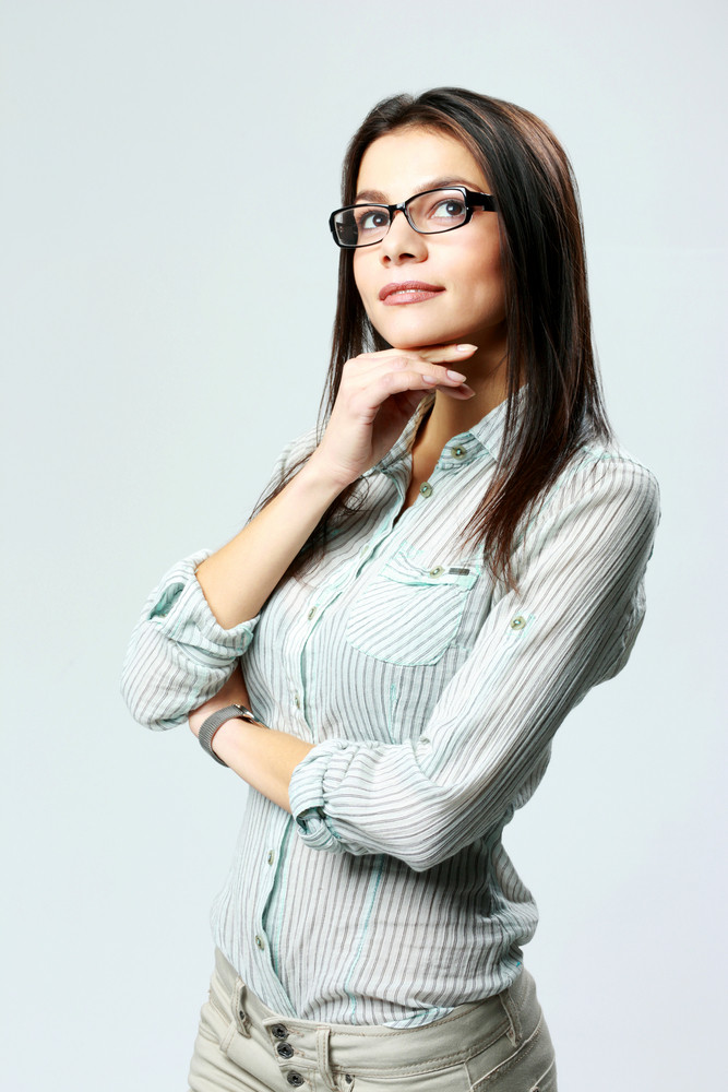Young thoughtful businesswoman wearing glasses standing and looking up on gray background