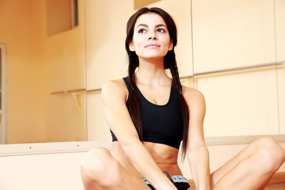 Young thoughtful fit woman sitting on the floor at gym