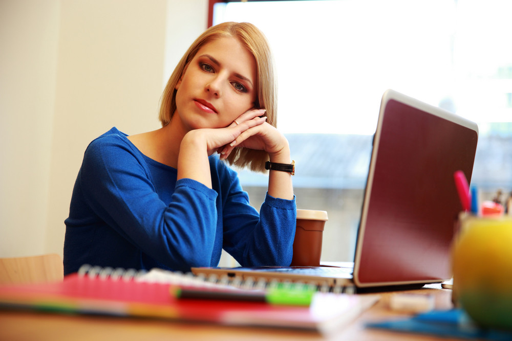 Young thoughtful woman sitting at the table with laptop and looking at camera