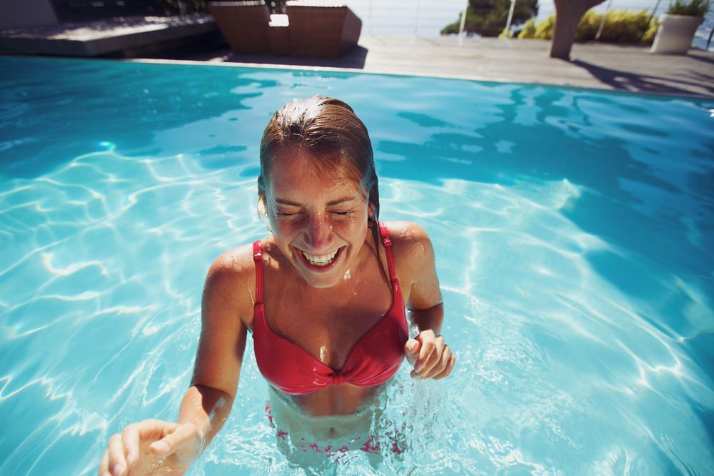 Young woman enjoying herself in a pool. Cheerful caucasian female wearing bikini in swimming pool.