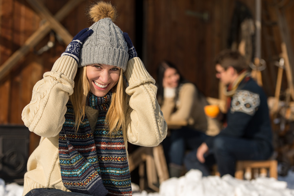 Young woman in winter hat spend time in snow cottage