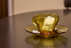 Empty cup with tea bag, spoon and sugar on table