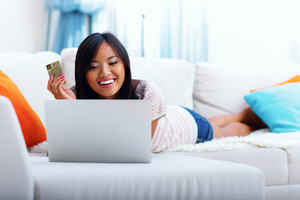 Happy asian woman shopping online at home with her credit card