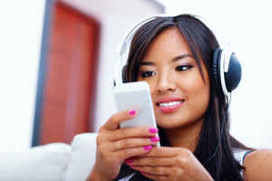 Asian woman with phones and headphones