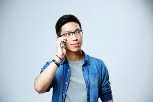 Young happy man in glasses talking on the phone on gray background