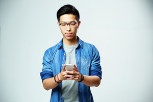 Young handsome asian man using smartphone on gray background