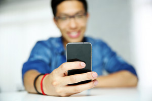 Portrait of a smiling asian man sitting at the table with smartphone