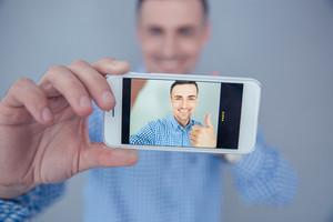 Smiling man making selfie photo