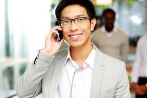 Portrait of a happy businessman talking on the smartphone in front of colleagues