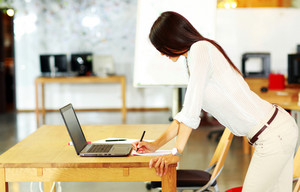 Standing woman using her laptop on the table at office