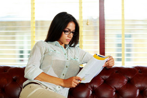 Portrait of a young businesswoman in glasses reading something
