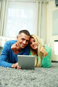 Happy couple lying on the carpet and using tablet computer together