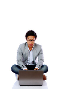 Young asian man sitting on the floor and using laptop over white background
