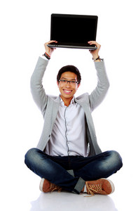 Happy asian man sitting on the floor and holding laptop
