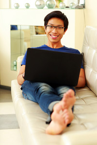 Young happy asian man lying on the sofa with laptop at home