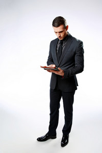 Businessman using tablet computer over gray background