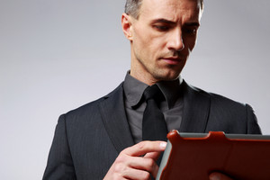 Smart businessman using tablet computer over gray background