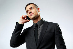 Portrait of a businessman speaking on cell phone isolated on a white background