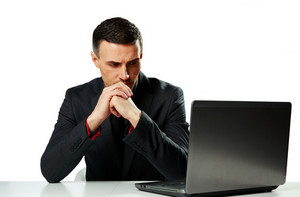 Pensive businessman sitting at the table and looking on laptop isolated on a white background