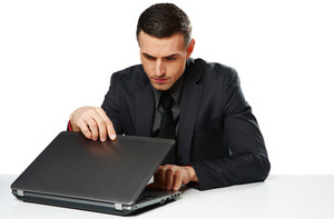 Confident businessman sitting at the table with laptop isolated on a white background