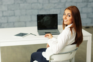 Confident happy businesswoman sitting at the table in office