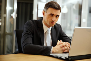 Pensive businessman sitting with laptop at office
