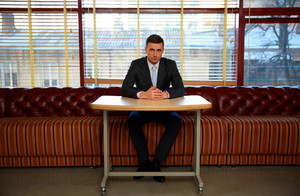 Confident businessman sitting at the table in office